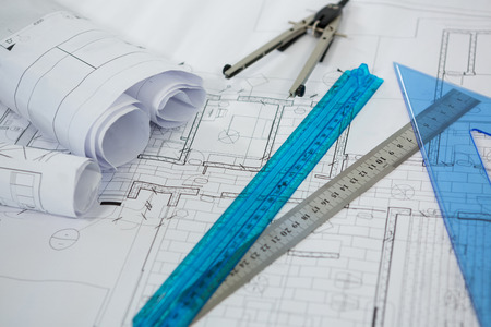 Close-up of blueprint with ruler, pencil and thumbscrew compasses