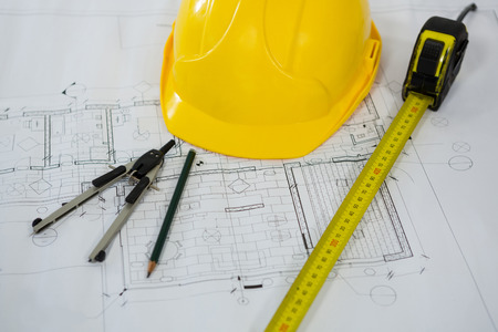 Close-up of blueprint with tape measure, pencil, thumbscrew compasses and hard hat