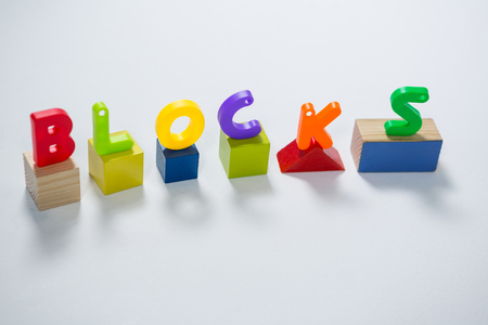Toy letters showcasing blocks on building blocks against white background Stock Photo