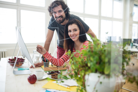 Portrait of graphic designers working over computer in office Stock Photo