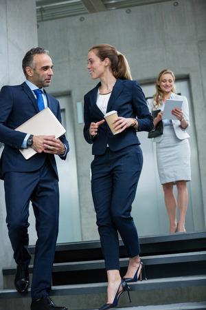 bajando escaleras: colegas de negocios que hablan el uno al otro mientras camina por las escaleras en el edificio de oficinas