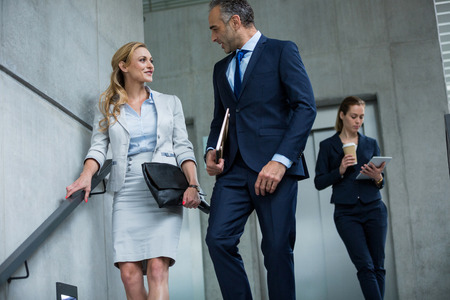 down the stairs: Business colleagues talking to each other while walking down stairs in office building
