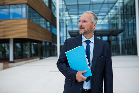 premises: Businessman carrying an official file in office premises Stock Photo
