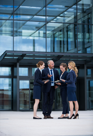 premises: Businesspeople standing and having a discussion in office premises Stock Photo