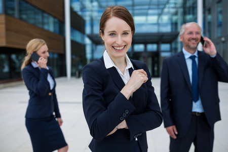 premises: Businesswoman smiling at camera while colleagues talking on mobile phones in office premises Stock Photo
