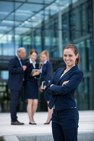 premises: Portrait of smiling businesswoman standing with arms crossed in office premises Stock Photo