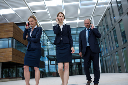 premises: Businesspeople talking on mobile phones in office premises Stock Photo