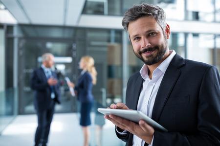 Portrait of businessman using digital tablet in office corridor Stock Photo