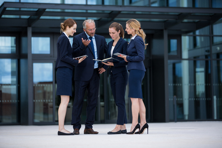 Businesspeople standing and discussing in office premises Stock Photo