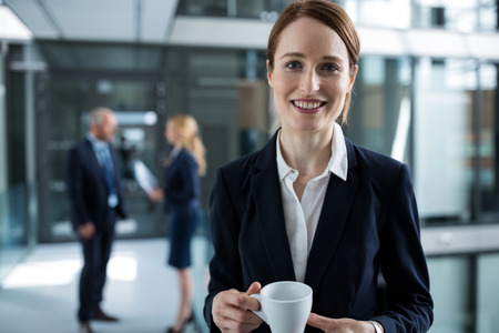 Portrait of businesswoman standing in office corridor with coffee cup