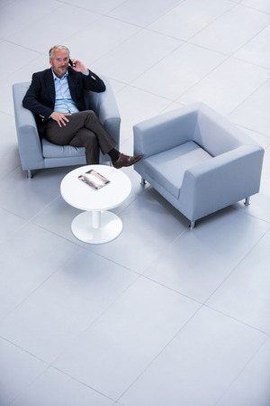 phone professional: Businessman sitting on a chair and talking on mobile phone in office