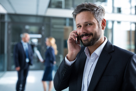 Portrait of smiling businessman talking on mobile phone in office corridor Stock Photo