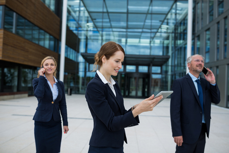 premises: Businesswoman using digital tablet while colleagues talking on mobile phone in office premises