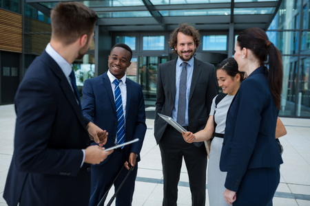 premises: Group of cheerful businesspeople having a conversation in office premises Stock Photo