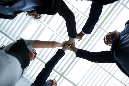 premises: Low angle view of happy businesspeople giving high five to each other in office premises