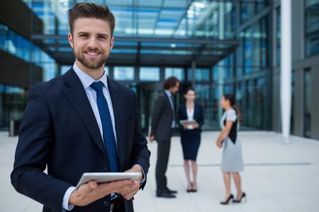 premises: Portrait of happy businessman holding digital tablet in office premises