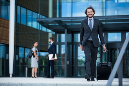 premises: Businessman walking in office premises with his suitcase Stock Photo