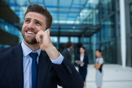 premises: Businessman talking on mobile phone in office premises