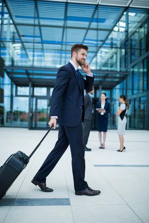 premises: Businessman holding suitcase talking on mobile phone in office premises