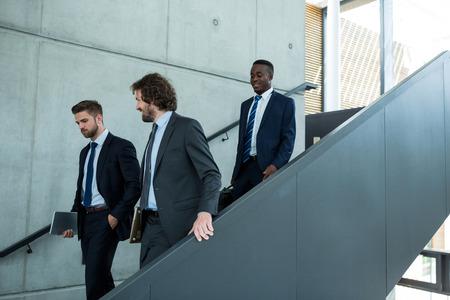 down the stairs: Grupo de hombres de negocios que suben por las escaleras en la oficina