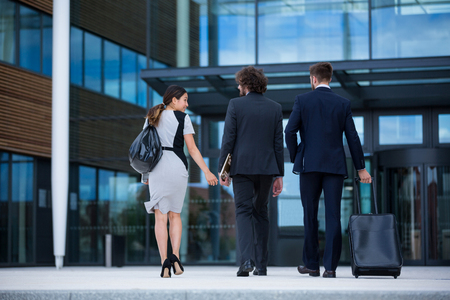 premises: Rear view of businesswoman with colleagues walking in office premises