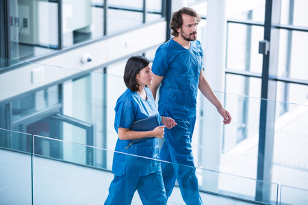 Surgeons walking in hospital corridor Stock Photo
