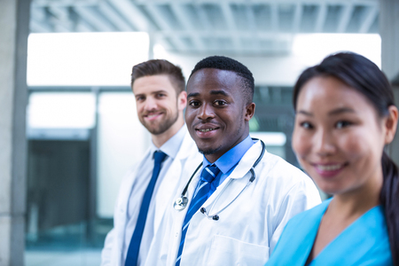 Portrait of confident doctor standing with colleagues in hospital