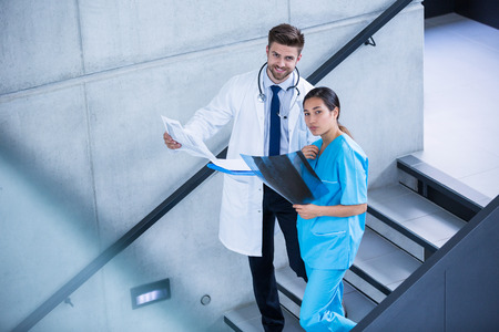 bajando escaleras: Doctor and nurse holding medical report and climbing down stairs in hospital