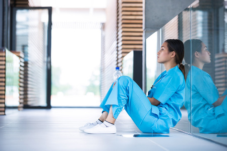 Depressed nurse sitting in hospital corridor Stock Photo