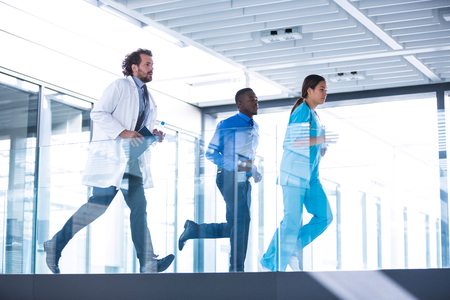 Businessman, doctor and nurse in hospital corridor during emergency Stock Photo