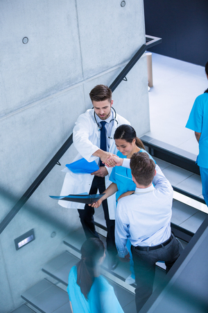 down the stairs: Doctor and nurse discussing over a report while climbing down stairs in hospital