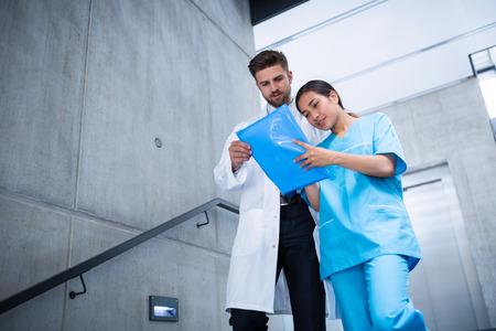 down the stairs: Médico y la enfermera discutiendo sobre un informe al subir por las escaleras en el hospital Foto de archivo