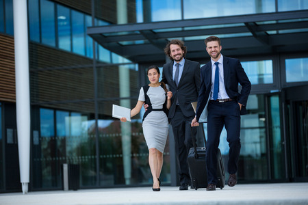 premises: Businesswoman with colleagues walking in office premises