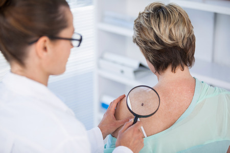 Dermatologist examining mole of female patient with magnifying glass in clinic