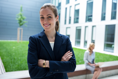 premises: Portrait of smiling businesswoman standing in office premises