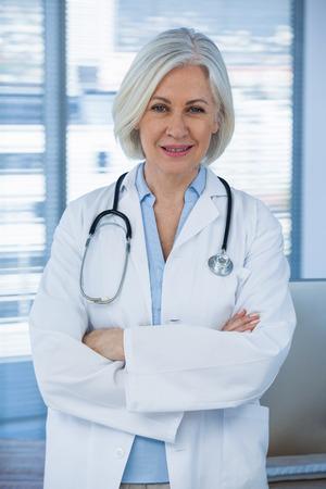 Portret van een lachende vrouwelijke arts die met armen omkruist op medisch kantoor