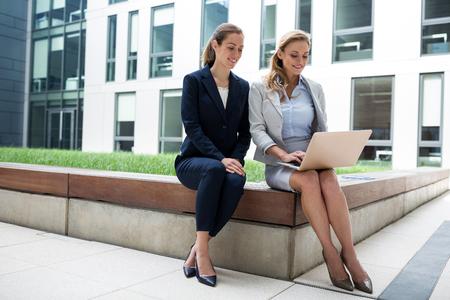 premises: Businesswomen sitting and using laptop in office premises