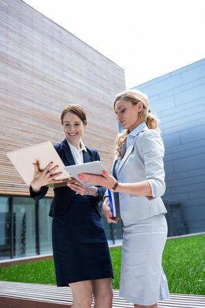 premises: Businesswomen using laptop and digital tablet in office premises Stock Photo