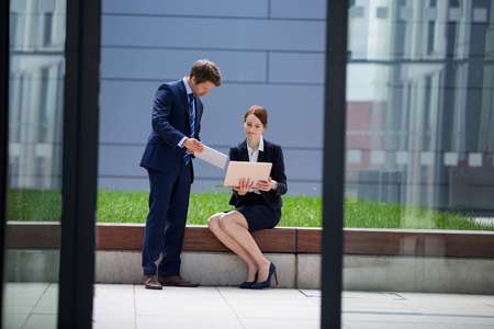 Businessman showing digital tablet to his colleague in office premises