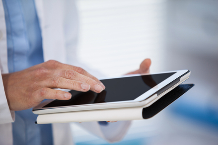 Mid section of doctor using digital tablet in clinic Stock Photo