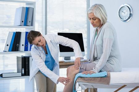 医師の診療所で患者の膝を調べる