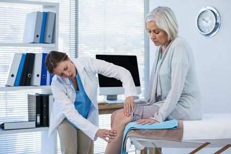 Medico che esamina ginocchio paziente in clinica Archivio Fotografico - 69596236