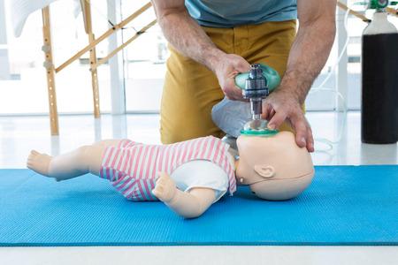 Paramédico practicando reanimación cardiopulmonar en maniquí en clínica Foto de archivo