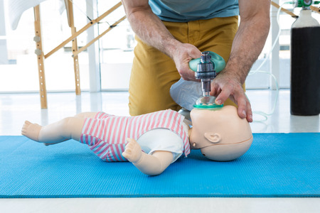 Paramedic practicing cardiopulmonary resuscitation on dummy in clinic