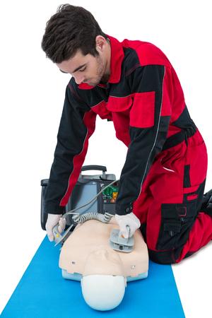 Paramedic practising resuscitation on dummy against white background Stock Photo