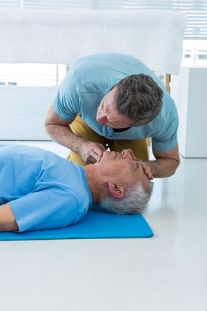 respiration: Paramedic performing resuscitation on patient in clinic Stock Photo