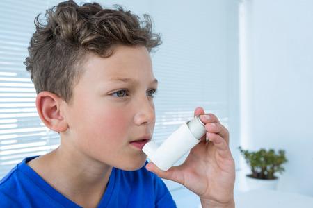 Boy using asthma pump in clinic