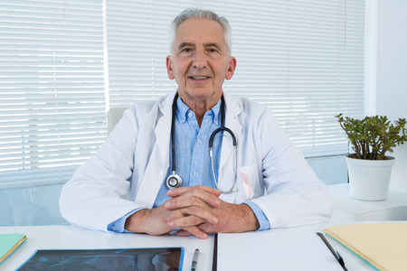 Portrait of smiling doctor sitting at table in clinic Stock Photo