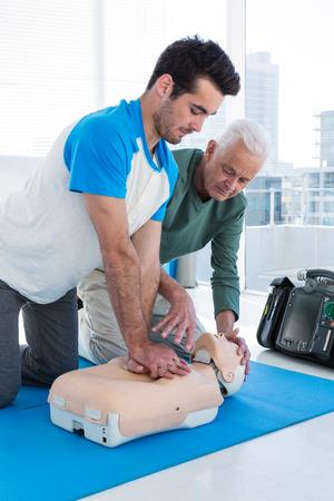 Paramedic training cardiopulmonary resuscitation to man in clinic Stock Photo