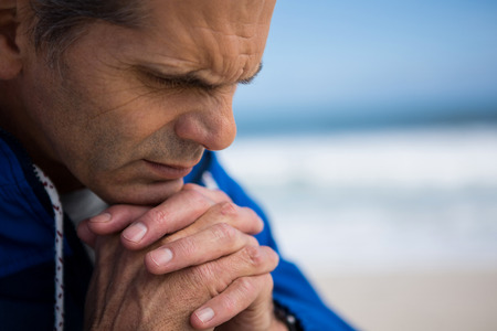 Mature man praying with hands clasped on beach